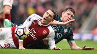 Bek Arsenal Hector Bellerin (kiri) mengerang kesakitan setelah ditekel gelandang Southampton Pierre-Emile Hojbjerg pada laga di Emirates Stadium, Minggu (8/4/2018). (AFP/Glyn Kirk)