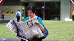 Seorang wanita membaca koran setelah sehari meninggalnya mantan PM Singapura, Lee Kuan Yew, Singapura, Selasa (24/3/2015). Lee meninggal pada hari Senin (23/3) di usia 91 tahun dan wajahnya menghiasi berbagai media cetak Singapura. (AFP PHOTO/Mohd FYROL)