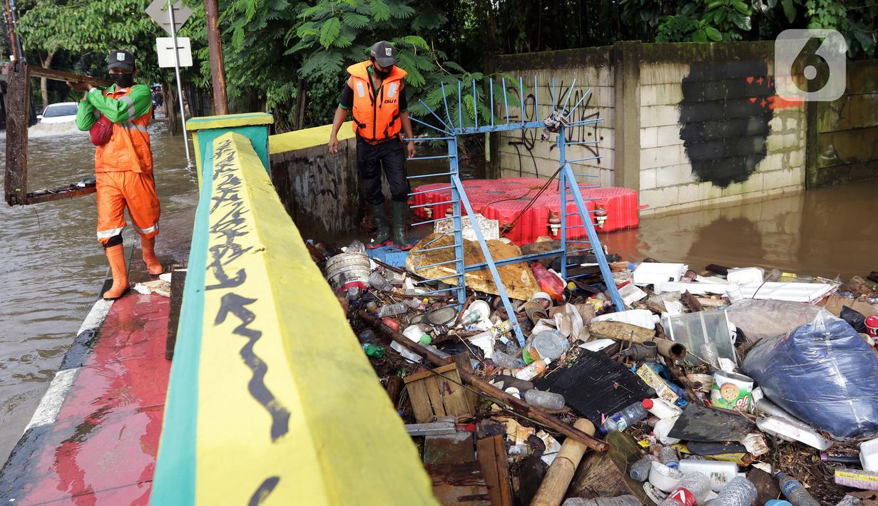 Petugas UPK Badan Air DLH Provinsi DKI Jakarta berjibaku membersihkan tumpukan sampah yang menghalangi aliran air Kali Mampang di Jalan Pejaten Raya, Jakarta, Sabtu (20/2/2021). Aliran air Kali Mapang di Jalan Pejaten Raya meluap akibat sumbatan tumpukan sampah. (Liputan6.com/Helmi Fithriansyah)