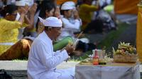 Seorang pria Hindu melakukan persembahyangan Hari Raya Galungan di Pura Jagat Natha di Denpasar, Bali (1/11). Galungan dimaknai sebagai hari kemenangan Dharma (Kebaikan) melawan Adharma (Keburukan). (AFP Photo/Sonny Tumbelaka)