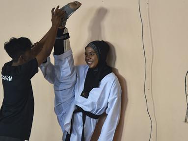 Peserta perempuan melakukan pemanasan sebelum bertanding pada Kejuaraan Terbuka Taekwondo di Banda Aceh (17/7/2019). Ratusan peserta mengikuti turnamen yang memperebutkan Piala Pemerintah Aceh. (AFP Photo/Chaideer Mahyuddin)