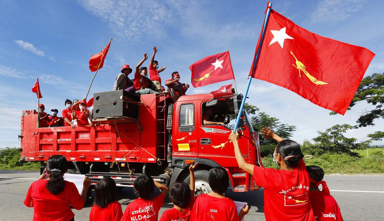 Pendukung partai National League for Democracy (NLD) pimpinan Aung San Suu Kyi mengibarkan bendera partai dan bersorak-sorai dari truk saat kampanye pemilihan umum bulan depan di Naypyitaw, Myanmar, Rabu (21/10/2020). (AP Photo/Aung Shine Oo)
