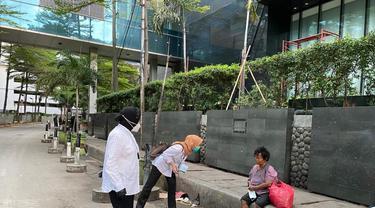 Menteri Sosial Tri Rismaharini atau Risma menyapa tunawisma di Jalan Sudirman, Jakarta Pusat, sebelum bekerja