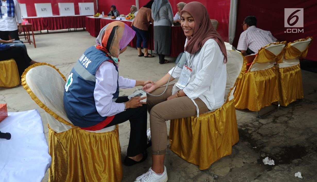 Petugas medis Puskesmas memeriksa tekanan darah petugas Kelompok Penyelenggara Pemungutan Suara (KPPS) yang bertugas saat pemungutan suara ulang di TPS 49 Rengas, Ciputat Timur, Tangsel, Rabu (24/4). Pemeriksaan untuk antisipasi menurunnya kesehatan fisik akibat kelelahan. (merdeka.com/Arie Basuki)