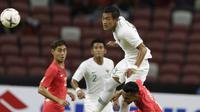 Kapten Indonesia, Hansamu Yama, menyundul bola saat melawan Singapura pada laga Piala AFF di Stadion Nasional, Singapura, Jumat (9/11). Indonesia menang atas Singapura. (Bola.com/M Iqbal Ichsan)