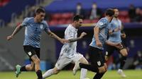 Pemain Argentina Lionel Messi menggiring bola dan melewati pemain Uruguay Jose Gimenez dalam laga Grup A Copa America di Stadion Nasional de Brasilia, Brasil, Sabtu, 19 Juni 2021. (AP Photo/Eraldo Peres)