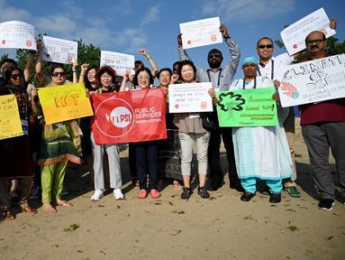 Massa mengangkat plakat saat kampanye perubahan iklim global di Pantai Sanur, Bali, Jumat (20/9/2019). Aksi ini diikuti oleh ratusan pekerja muda dari 21 negara Asia Pasifik yang tergabung dalam federasi serikat pekerja global Public Services International (PSI). (SONNY TUMBELAKA/AFP)