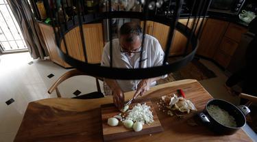 Hasan Titi (56) membantu istrinya, Samar Titi memasak hidangan di dapur rumah mereka di Kota Nablus, Tepi Barat, 30 Maret 2020. Di Palestina, para perempuan yang biasanya melakukan pekerjaan memasak, namun kondisi itu berubah di tengah penerapan karantina wilayah (lockdown). (Xinhua/Ayman Nobani)