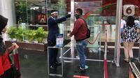 Petugas mengecek suhu tubuh pengunjung di pusat perbelanjaan di Depok, Jawa Barat, Rabu (17/6/2020). Mulai 16 Juni 2020, sejumlah pusat perbelanjaan di Kota Depok kembali beroperasi selama masa PSBB proporsional, namun tetap dengan memerhatikan protokol kesehatan. (Liputan6.com/Immanuel Antonius)