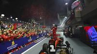 Pembalap Ferrari Sebastian Vettel berselebrasi di atas mobilnya setelah memenangkan balapan F1 GP Singapura di Sirkuit Jalan Marina Bay, Singapura (22/9/2019). Vettel kini memegang rekor kemenangan terbanyak di Singapura (2011, 2012, 2013, 2015,2019). (AP Photo/Lim Yong Teck)
