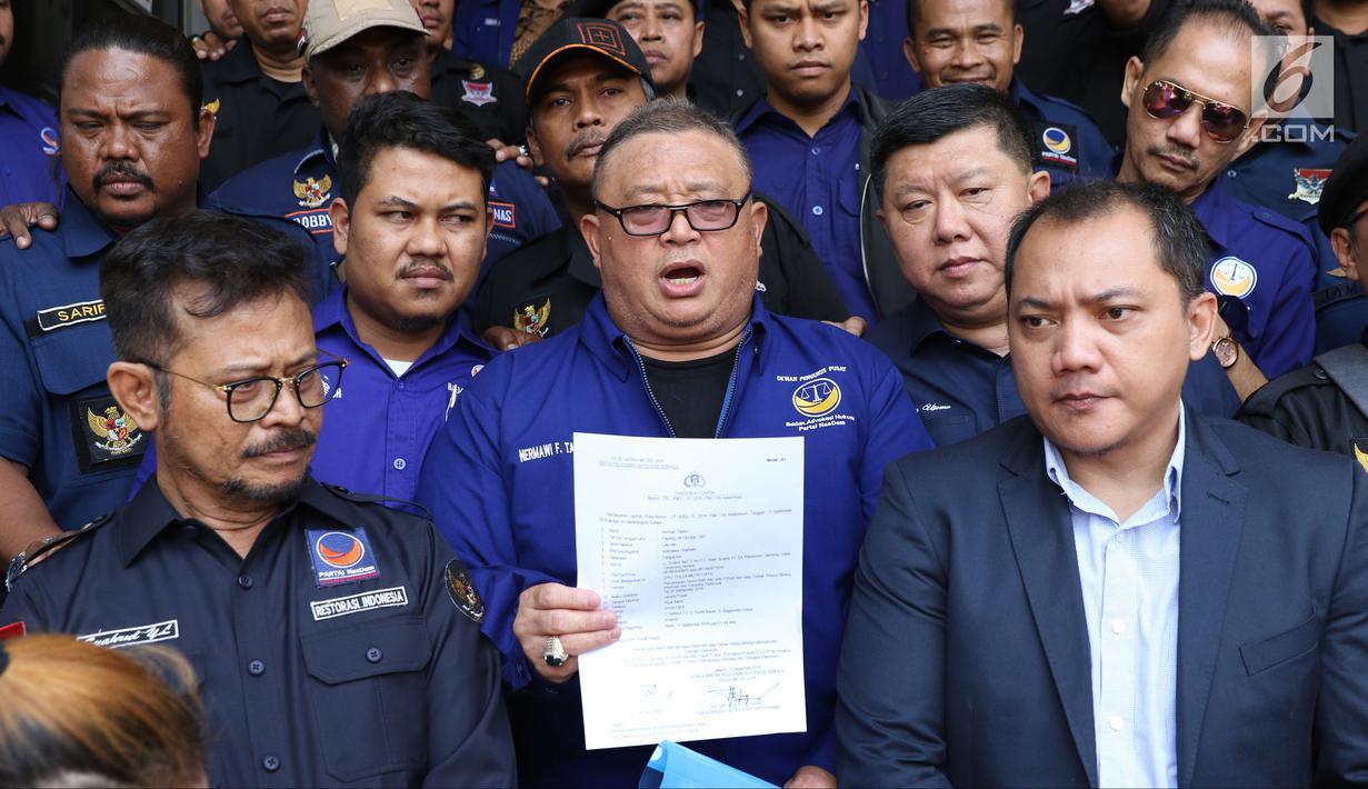 Kuasa Hukum Partai Nasdem, Herman Taslim (tengah) memberi keterangan usai membuat surat laporan di Polda Metro Jaya, Senin (17/9). Partai Nasdem melaporkan Rizal Ramli atas dugaan pencemaran nama baik dan fitnah. (Liputan6.com/Helmi Fithriansyah)