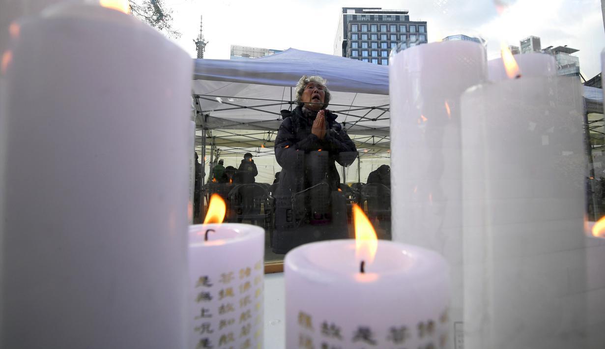 Seorang wanita berdoa untuk keberhasilan anak dan kerabatnya dalam mengikuti tes kemampuan Skolastik College tahunan di Seoul (23/11). Mereka mendoakan anaknya agar dapat lulus ujian masuk perguruan tinggi. (AFP Photo/Jung Yeon-Je)