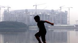 Seorang anak bermain di pinggir Waduk Cincin yang berlatar pembangunan Jakarta International Stadium (JIS), Sabtu (19/6/2021). Pembangunan JIS sudah memasuki tahap pemasangan rangka atap dengan bentang mencapai 269 meter dan ditarget selesai Desember 2021. (Liputan6.com/Helmi Fithriansyah)