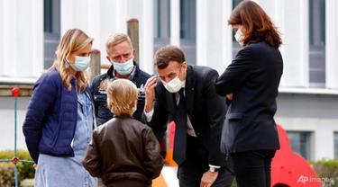 Presiden Prancis Emmanuel Macron berbicara dengan seorang anak saat dia mengunjungi departemen psikiatri anak di rumah sakit Reims, Prancis timur, pada 14 April 2021.
