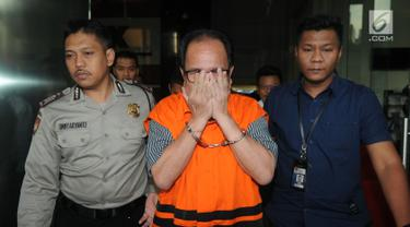 Pihak swasta Joe Fandy Yoesman alias Asiang menutupi wajahnya usai menjalani pemeriksaan di Gedung KPK, Jakarta, Kamis (18/7). Asiang resmi ditahan untuk mempermudah pemeriksaan terkait terkait kasus dugaan suap pengesahan APBD 2017-2018 Provinsi Jambi. (merdeka.com/Dwi Narwoko)