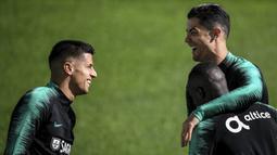 Penyerang Portugal, Cristiano Ronaldo tertawa dengan bek Joao Cancelo dan Bruma Bangna  selama mengikuti latihan tim di stadion Algarve di Faro (13/11/2019). Portugal akan bertanding melawan Lithuania pada Grup B Kualifikasi Piala Eropa 2020 di Estádio Algarve. (AFP Photo/Patricia De Melo Moreira)