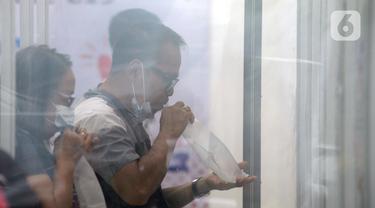 Calon penumpang meniup kantong saat dilakukan tes COVID-19 dengan GeNose C19 di Stasiun Pasar Senen, Jakarta, Selasa (23/2/2021). PT KAI memberikan pelayanan tes COVID-19 dengan GeNose C19 bagi calon penumpang kereta jarak jauh untuk memutus rantai penyebaran virus corona. (merdeka.com/Imam Buhori)