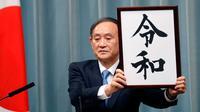 Sekretaris Kabinet Jepang, Yoshihide Suga menunjukkan plakat nama era baru Kekaisaran Jepang, Reiwa, di Tokyo, Senin (1/4). Reiwa, menjadi nama era yang baru yang mengganti Era Heisei seiring persiapan pengunduran diri Kaisar Akihito pada 31 April mendatang. (AP/Eugene Hoshiko)