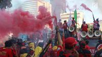 Sejumlah buruh menyalakan bom asap saat menutup aksi Hari Buruh Internasional di Jalan Medan Merdeka Barat, Jakarta, Rabu (5/1/2019). Aksi May Day 2019 di Jakarta ditutup oleh buruh dengan menyalakan kembang api sebagai simbol berjalannya demo dengan damai. (Liputan6.com/Helmi Fithriansyah)