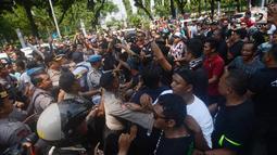 Massa driver taksi online yang tergabung dalam Aliando terlibat aksi saling dorong dengan polisi saat menggelar demo di Jalan Medan Merdeka Barat, Jakarta, Rabu (28/3). Dalam aksinya mereka sempat bersitegang dengan polisi. (Merdeka.com/Imam Buhori)