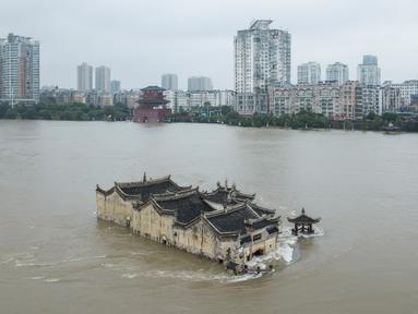 Foto pada 19 Juli 2020 menunjukkan kuil Guanyinge berumur 700 tahun yang dibangun di atas batu, terendam banjir akibat meluapnya sungai Yangtze di Wuhan, provinsi Hubei. Hujan lebat sejak bulan Juni telah menyebabkan sedikitnya 141 orang tewas dan memaksa hampir 15 juta orang dievakuasi. (STR/AFP)