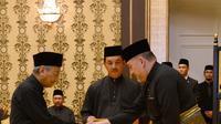 Perdana Menteri Malaysia baru, Mahathir Mohamad (kiri) bersalaman dengan Raja Malaysia Muhammad V saat prosesi sumpah jabatan di Istana Nasional di Kuala Lumpur (10/5). (AFP Photo/ Istana Nasional Malaysia)