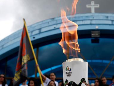 Warga menyaksikan parade obor Olimpiade yang melintas di Itamaraju, Kota Bahia , Brasil,(19/5/2016). Olimpiade akan dilaksanakan di Rio De Jeneiro.  (AFP/Marcos de Paula)