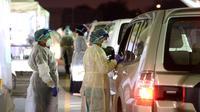 Para petugas medis bersiap mengambil sampel usap dari para pengemudi di pusat tes COVID-19 lantatur (drive-thru) di Kegubernuran Farwaniya, Kuwait, 18 November 2020. Total kasus COVID-19 di Kuwait menjadi 138.337 dan kematian menjadi 857. (Xinhua/Asad)