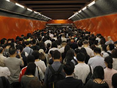 Penumpang mengantri di platform kereta bawah tanah di Hong Kong (30/7/2019). Para pengunjuk rasa telah mengganggu layanan kereta bawah tanah pada pagi hari perjalanan dengan menghalangi pintu-pintu masuk kereta dan mencegah mereka meninggalkan stasiun. (AP Photo/Vincent Yu)