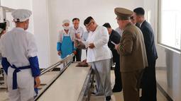 Pemimpin Korea Utara Kim Jong-un (tengah) memeriksa salah satu produk ransum militer saat mengunjungi Pabrik No. 525 di Korea Utara, Rabu (25/7). (STRINGER/AFP/KCNA VIA KNS)