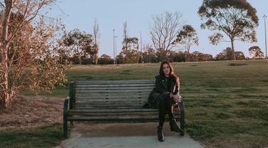 Saat liburan ke Australia, Raisa tampak duduk di sebuah kursi di Albert Park and Lake dengan santainya. Menggunakan busana serba hitam, ia tampak cantik diterpa matahari dengan latar taman dan pepohonan. (Liputan6.com/IG/@raisa6690)