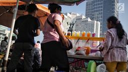 Pedagang kaki lima (PKL) berjualan saat pelaksanaan CFD di kawasan Bundaran HI, Jakarta, Minggu (5/5/2019). Kurangnya pengawasan petugas menyebabkan banyak PKL berjualan tidak pada tempat yang telah di sediakan Pemprov DKI sehingga mengganggu aktivitas warga berolahraga. (Liputan6.com/Faizal Fanani)