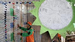 Petugas UPK Badan Air DLH DKI Jakarta saat merapikan susunan instalasi botol yang menghiasi pos di Pasar Rebo, Jakarta, Selasa (12/3). Petugas memanfaatkan botol plastik bekas untuk membangun pos cantik. (merdeka.com/Iqbal Nugroho)