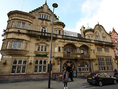 Pejalan kaki berjalan melewati pub Philharmonic Dining Rooms di Liverpool, Inggris pada 11 Februari 2020. Tempat nongkrong favorit anggota The Beatles ini mendapat status cagar budaya Grade I dari pemerintah Inggris. (Paul ELLIS / AFP)