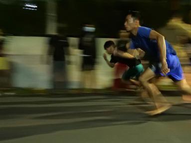 Dua pebalap lari liar adu lari berjarak 100 meter di Jalan Raya Ciri Mekar, Cibinong, Bogor, Sabtu (12/9/2020) dini hari. Menurut mereka balap lari liar ini lebih positif dari balap motor dan mobil liar, walaupun kegiatan itu mengganggu lalu lintas di kawasan tersebut. (Liputan6.com/Herman Zakharia)