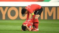 Son Heung-min menghibur rekannya di Timnas Korea Selatan, Im Beom-hwang, setelah tersingkir dari Piala Asia 2019 akibat kalah 0-1 dari Qatar di perempat final yang dimainkan di Zayed Sports City Stadium, Abu Dhabi (25/1/2019). (AFP/Khaled Desouki)