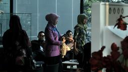 Istri Bupati Bogor, Eli Halimah (berbaju ungu, tengah) berada di lobi gedung KPK, Jakarta, Jumat (9/5/2014) (Liputan6.com/Johan Tallo)