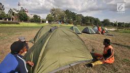 Petugas PPSU mendirikan tenda di Cipinang Melayu, Jakarta, Minggu (30/12). Pendirian puluhan tenda di RTH tersebut untuk kemah massal dalam menyambut malam Tahun Baru yang juga diisi dengan kegiatan doa bersama. (Merdeka.com/ Iqbal S. Nugroho)