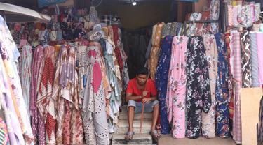 Pekerja menunggu pembeli di salah satu toko di Pasar Cipadu, Tangerang, Selasa (2/3/2021). Pandemi Covid-19 membuat industri tekstil dan pakaian jadi mengalami pertumbuhan negatif 8, 8 persen sepanjang 2020 dengan kinerja ekspor yang berkontraksi 17 persen. (Liputan6.com/Angga Yuniar)