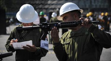 Tentara mencatat nomor seri dan model senjata otomatis selama penghancuran senjata api yang disita dari penjahat atau diserahkan oleh orang-orang, di Kamp Militer 1-A di Kota Meksiko, (1/8). (AFP Photo/Bernardo Montoya)