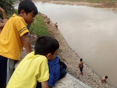 Anak-anak melihar teman-temannya  bermain di Bantaran sungai Kanal Banjir Barat, Tanah Abang, Jakarta, Sabtu (4/1/2020). Minimnya pengawasan  membuat anak-anak kerap bermain di tempat berbahaya yang berpotensi mengancam keselamatan mereka. (Liputan6.com/Angga Yuniar)