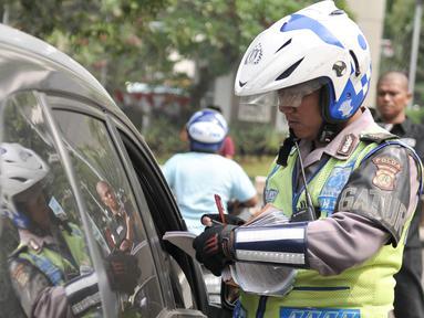 Petugas menilang pengendara mobil yang melanggar aturan pembatasan kendaraan sistem ganjil genap di kawasan Sudirman, Jakarta, Selasa (30/8). Hari ini resmi diberlakukan denda bagi pelanggar aturan sistem ganjil genap. (Liputan6.com/Yoppy Renato)