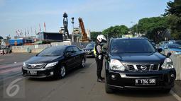 Petugas menjelaskan aturan sistem ganjil genap kepada pengendara mobil yang melintas di Bundaran Senayan, Jakarta, Rabu (31/8). Sejak kemarin mulai diberlakukan sanksi kepada pengendara yang melanggar aturan ganjil-genap. (Liputan6.com/Gempur M Surya)