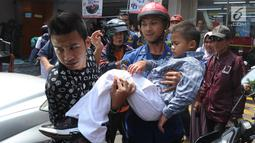 Petugas Damkar dari Pos Pesanggrahan membawa murid TK, Fathur  usai menyelamatkannya dari terjepit kaca pintu ATM Bank BNI di Jalan M. Saidi, pesanggrahan, Jakarta Selatan, Senin (5/8/2019). Fathur mengalami luka pada tanggannya selanjutnya dibawa ke rumah sakit. (merdeka.com/Arie Basuki)