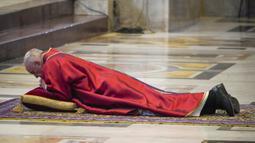 Paus Fransiskus berbaring dalam doa saat memimpin misa Jumat Agung di Basilika Santo Petrus, Vatikan, Jumat (10/4/2020). Pandemi virus corona COVID-19 yang melanda dunia membuat perayaan Jumat Agung berlangsung terbatas untuk menghindari penyebaran penyakit. (AP Photo/Andrew Medichini, Pool)