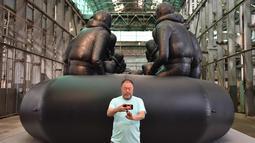 """Seniman asal China, Ai Weiwei berselfie di depan karyanya yang berjudul """"Law of the Journey 2017""""di preview pers Biennale ke 21 di Sydney (12/3). Biennale akan berlangsung mulai 16 Maret - 11 Juni 2018. (AFP Photo/Peter Parks)"""