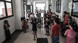 Anak-anak bermain di lorong kelas saat mengungsi di SDN 01 Kampung Melayu, Jakarta, Minggu (21/2/2021). Sudah 2 hari ratusan warga dari 4 RW di Kelurahan Kampung Melayu mengungsi di gedung sekolah lantaran banjir yang merendam rumah mereka tak kunjung surut. (merdeka.com/Iqbal S Nugroho)