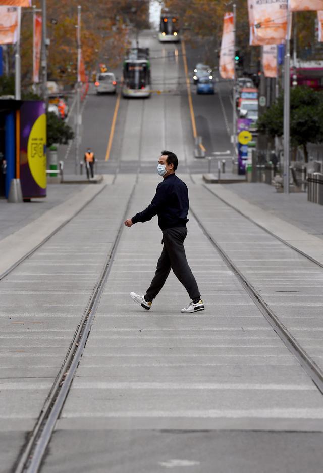 Seorang pria melintasi Bourke Street Mall yang biasanya sibuk di Melbourne ketika penduduk kota kembali menjalani lockdown selama 7 hari, Jumat (28/5/2021). Melbourne kembali menerapkan lockdown untuk keempat kalinya setelah wabah COVID-19 menyebar cepat di wilayah tersebut. (William WEST/AFP)