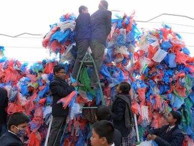 Relawan Nepal dan siswa sekolah membuat replika Laut Mati dari plastik daur ulang di Kathmandu pada 5 Desember 2018. Mereka mengikat 100.000 kantong plastik bekas berwarna-warni untuk upaya pembuatan rekor dunia baru. (PRAKASH MATHEMA / AFP)