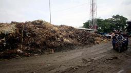 Warga saat melintas di dekat gunungan sampah di Pasar Induk Kramat Jati, Jakarta, Kamis (8/1/2015). (Liputan6.com/Faizal Fanani)